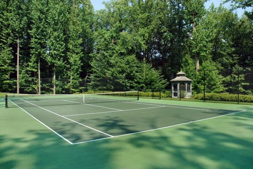 This is the gorgeous tennis court of the property adorned with tall pine trees that go well with the green floor of the court. Images courtesy of Toptenrealestatedeals.com.