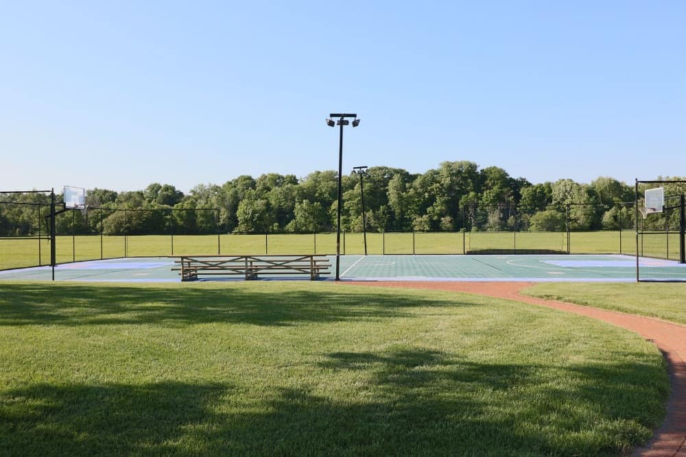 This is a lovely basketball court that also doubles as a tennis court. It is surrounded by tall fences with professional outdoor lighting and a wide lawn of grass with a walkway. Images courtesy of Toptenrealestatedeals.com.