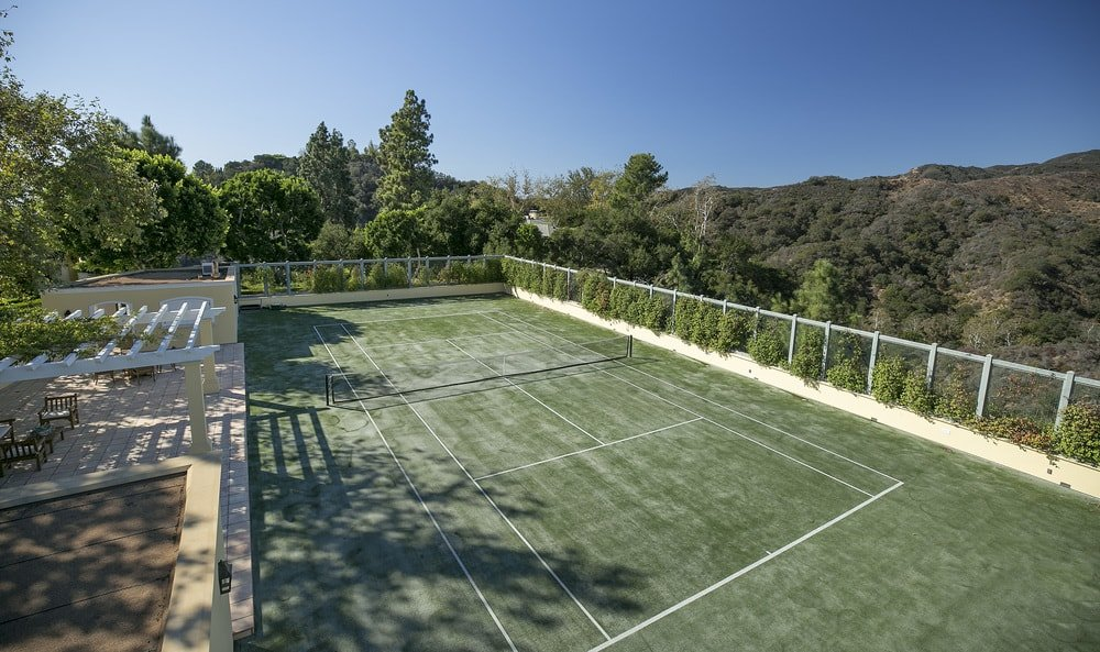 The large outdoor tennis court has a green floor to match the surrounding lush tall trees and shrubs. Image courtesy of Toptenrealestatedeals.com.