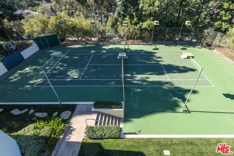 This is the top view of this tennis court that also doubles as a basketball court. It has lovely green flooring to match the surrounding lush green landscape.
