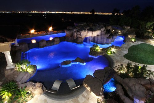With proper lighting, your backyard water park will glow at night. This looks great and can be a large draw for nighttime swimming. Who would not be drawn in by the glowing allure of the water here?