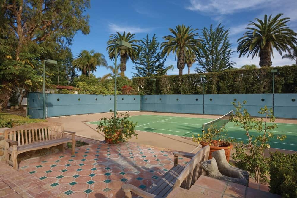 The property offers a tennis court with a sitting area on the side. The court is surrounded by charming terracotta <a class=