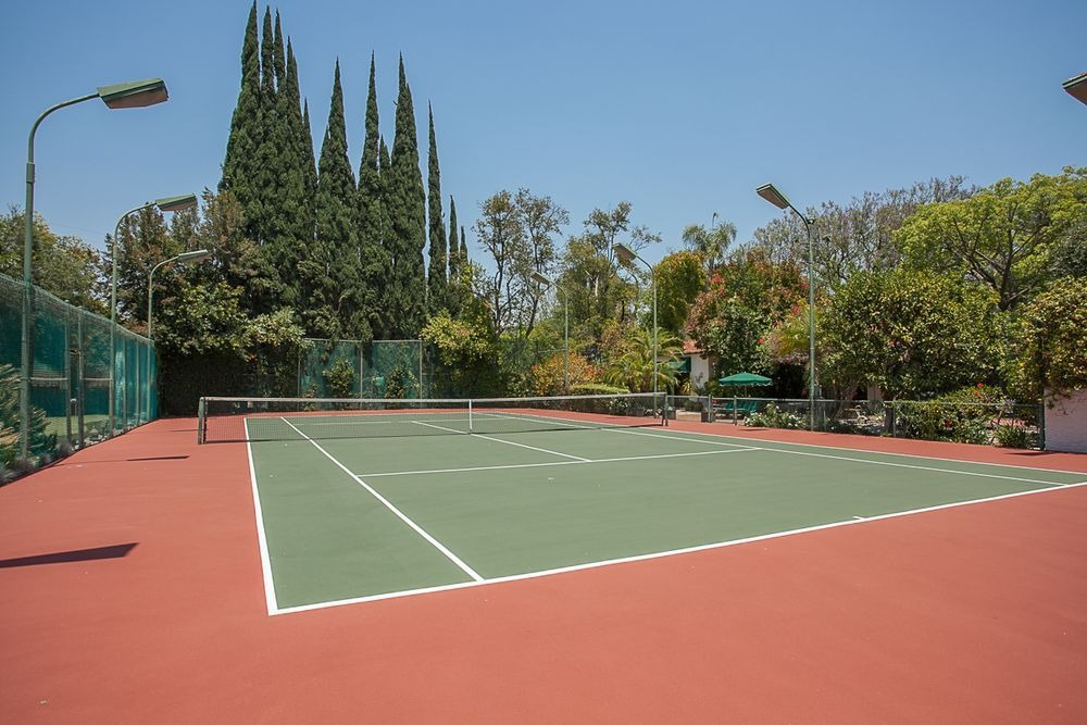 A tennis court set on the side of the home's mini golf course surrounded by thick shrubs and tall trees that contrast the terracotta tone of the court. Image courtesy of Toptenrealestatedeals.com.
