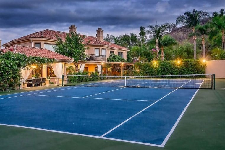 This is the gorgeous blue tennis court just beside the lovely home. This is adorned with warm outdoor lighting and a lush landscaping.