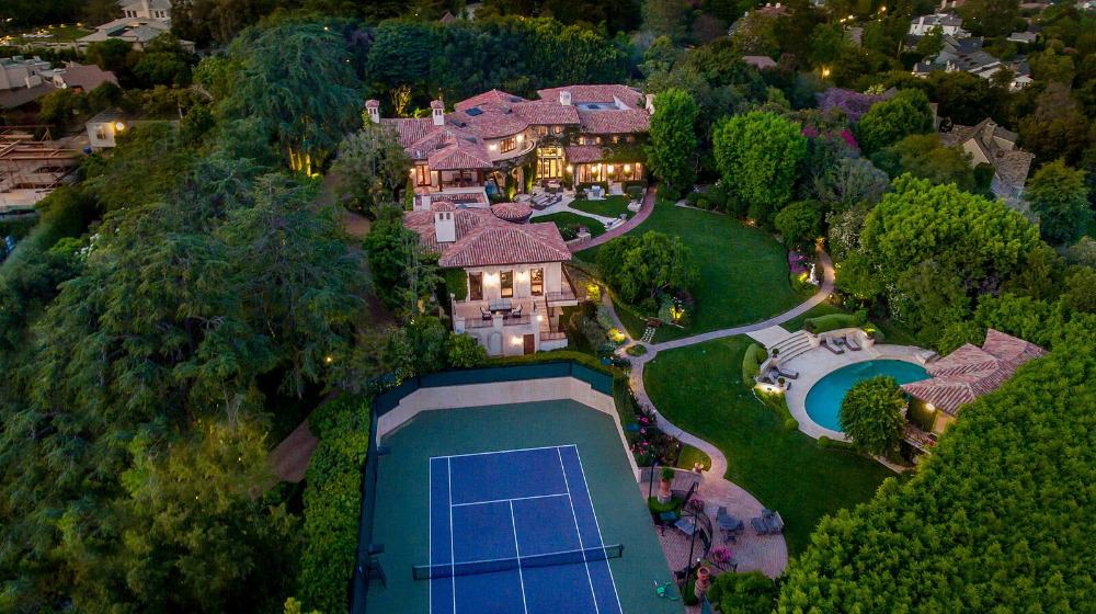 This aerial view of the property showcases the lovely blue tennis court beside the house. It is surrounded by green grounds and has terracotta walkways as well as a sitting area on the side. Images courtesy of Toptenrealestatedeals.com.