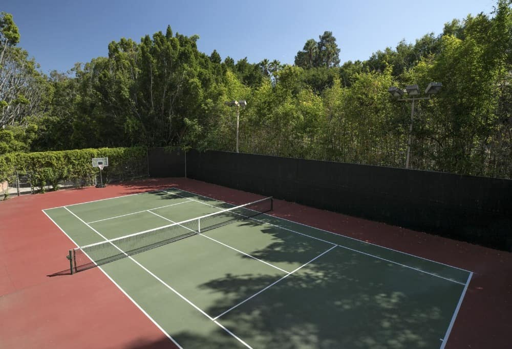 There's a whole tennis court set on the home's backyard. It has tall fences adorned by creeping plants and tall mature trees that give shade and charm to the area. Images courtesy of Toptenrealestatedeals.com.