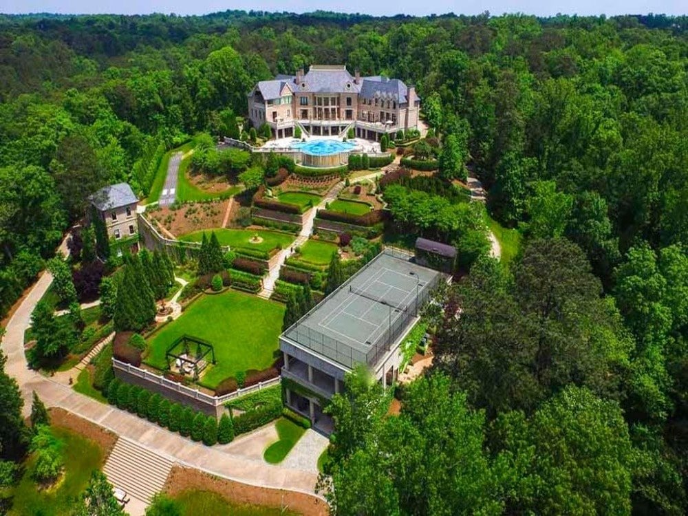 This is an aerial view of the mansion boasting its magnificent architecture and landscape designs. Here you will also see the large professional-size gray tennis court by the thick forest of trees.Images courtesy of Toptenrealestatedeals.com.