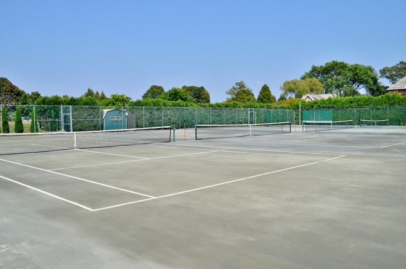 This is a massive open area that fits three tennis courts. The whole area is fenced with net adorned with tall green trees that complement the concrete flooring.