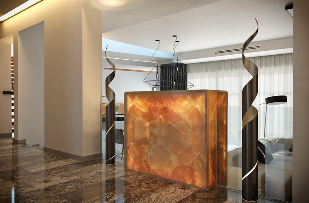 Seen from the hallway, the glowing drink shelf in the living room is another bold example of the amber stone element, standing out amidst the sleek surroundings. The hallway features dark marble flooring.