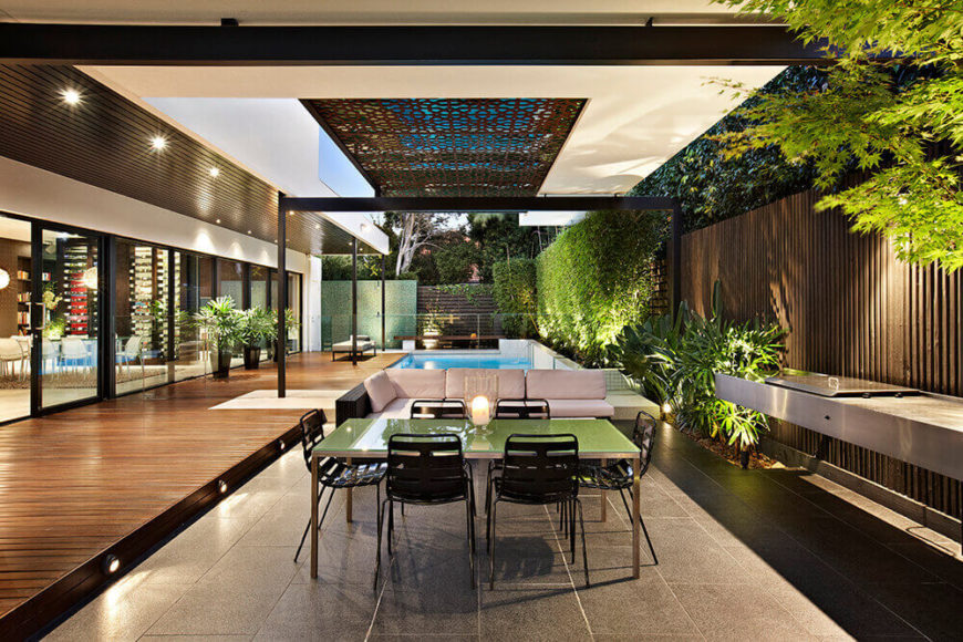 The incredibly open design of the home means that spaces like this outdoor dining area can be as well accommodated as those inside. To the left is the lengthy deck and home, while a grill and cooking countertop appears at right.