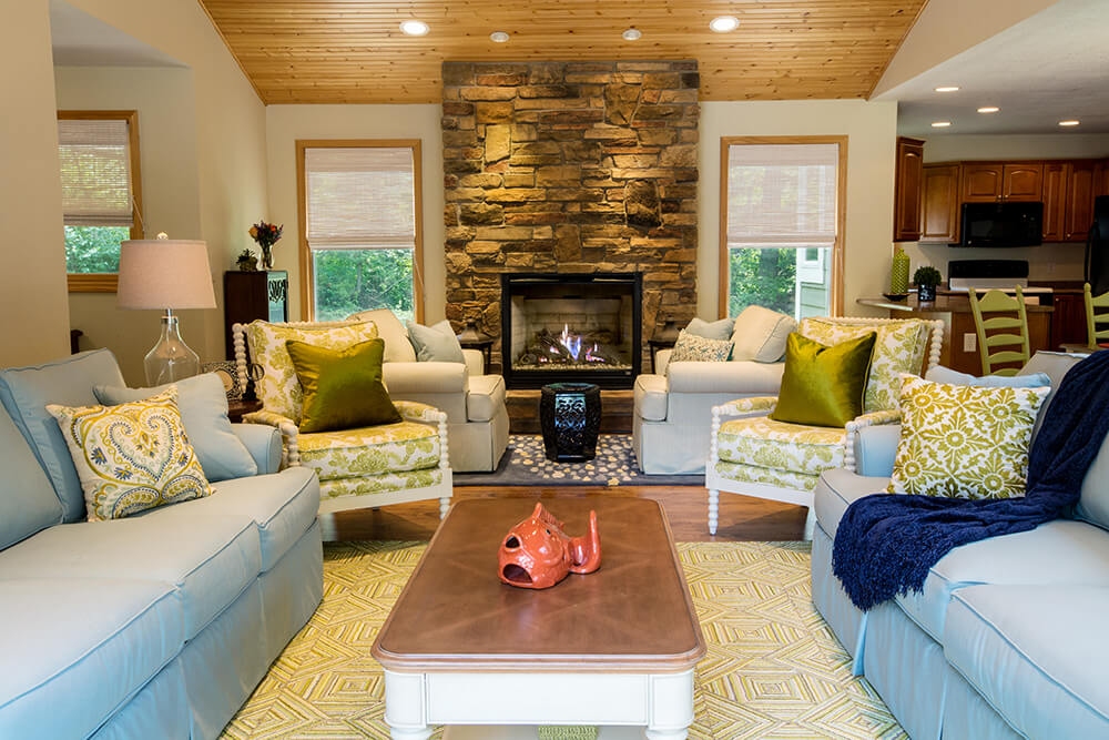At the center of this broad open space, we see the stone fireplace dominating the visual scale of the room, with abundant natural light keeping everything highlighted.