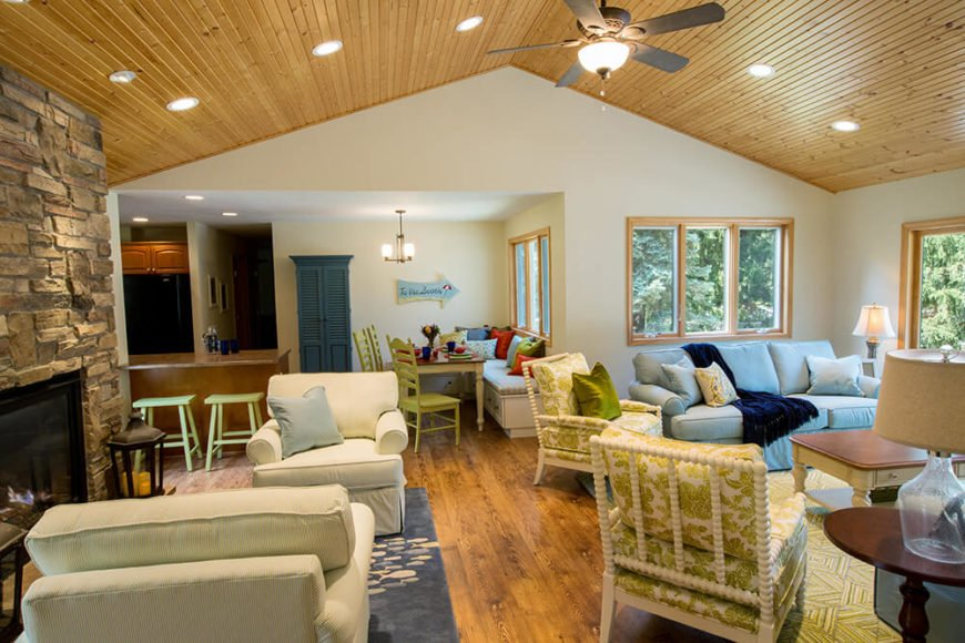 Turned to the side, we see the kitchen and the hallway leading toward bedrooms. At center is the breakfast nook space, with colorful chairs and throw pillows adding a bit of variety to the palette.