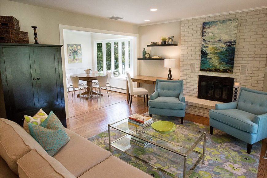 The living room features a subtly varied set of furniture over its hardwood flooring. At right, a small writing desk sits below built-in shelves next to the brick fireplace.
