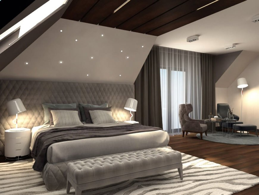 The primary bedroom is a huge space, incorporating a sleeping area and distinct relaxing space with armchairs and table. The bed is framed by a massive wall-size headboard and overlooked by star-like embedded lights.
