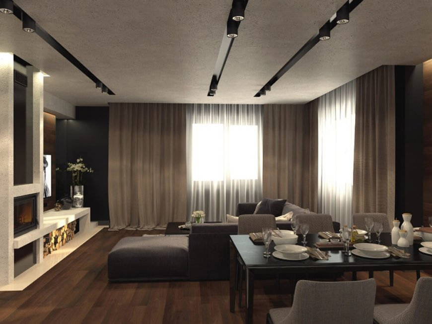 The living room centers on a large contemporary sectional sofa in dark grey, bringing subtle contrast to the space. Large windows cast natural light over the rich hardwood floors from end to end.