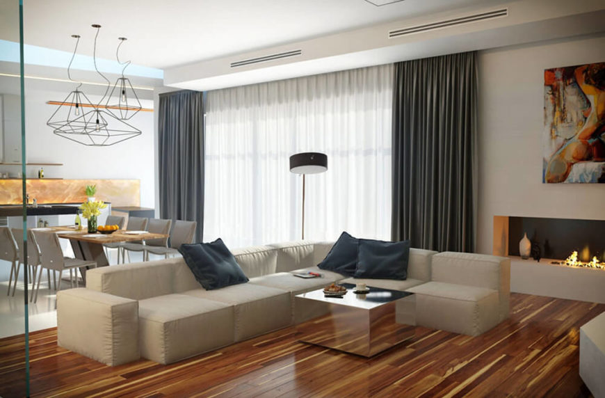The large, cushy white sectional here stands in sharp contrast to the sharp mirrored coffee table at center. Juxtapositions like this define the look of the home interior.