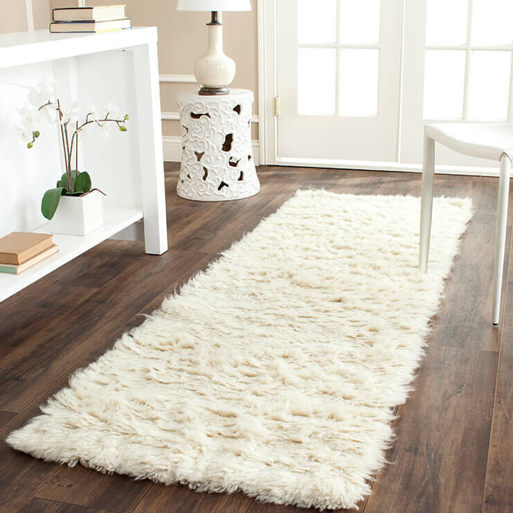 A fluffy white shag rug serves as a counterpoint to chilly floors and is the perfect spot for enjoying a book or savoring a cup of tea. This plush rug is an inviting landing pad for pets and humans alike.