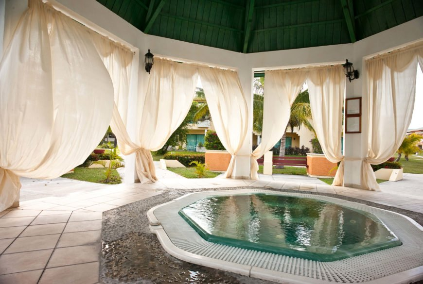 This large space is an elegant and sophisticated gazebo with a private hot tub right in the center. The curtains between the pillars are great decoration that give the space a breezy and relaxed appeal.