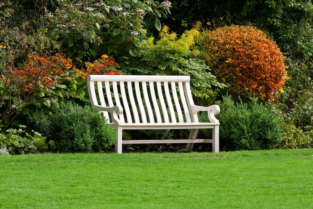 This is a wood bench coated in white paint to protect it from wear and tear. It can withstand the rain without deteriorating.