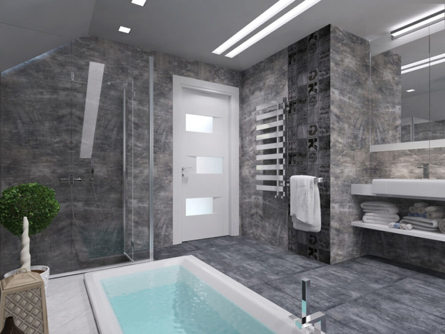 The bathroom also features a sleek glass enclosed walk-in shower, as well as sets of glossy white shelving beneath the floating vanity.