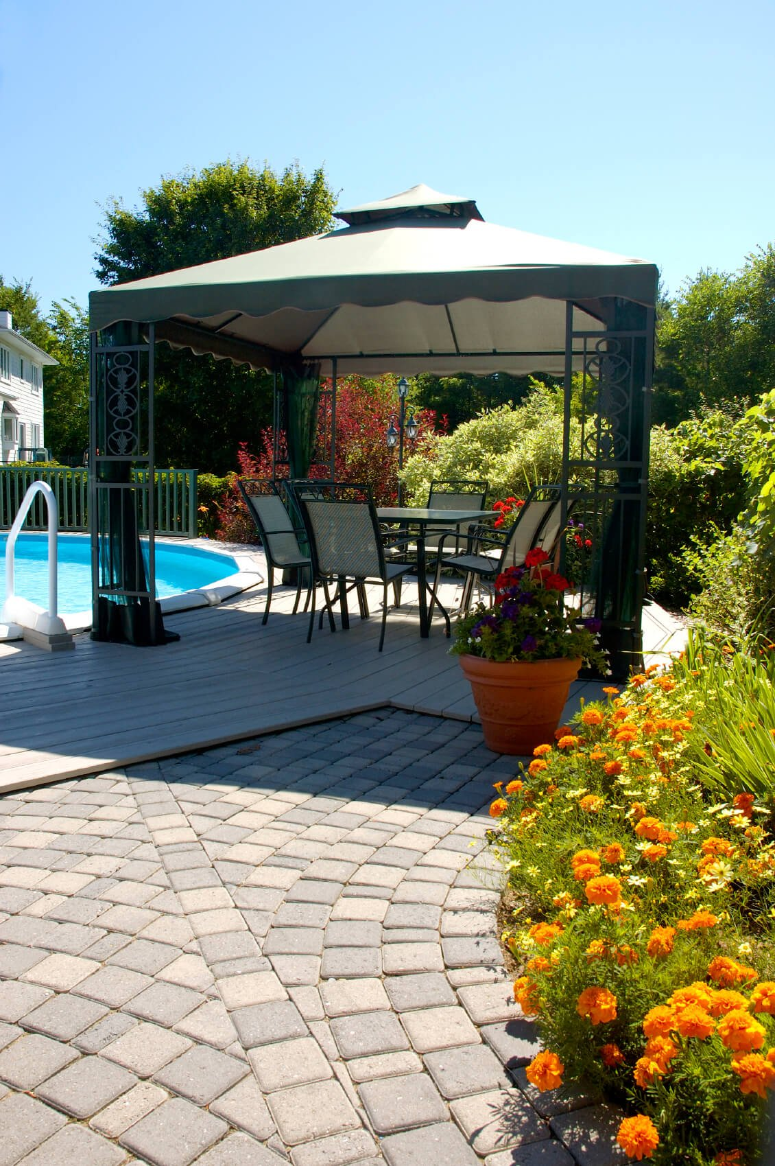 This cloth top gazebo is set up on the side of the pool, providing a shady spot for a relaxing gathering. What better on a sunny day than sitting poolside with your friends?