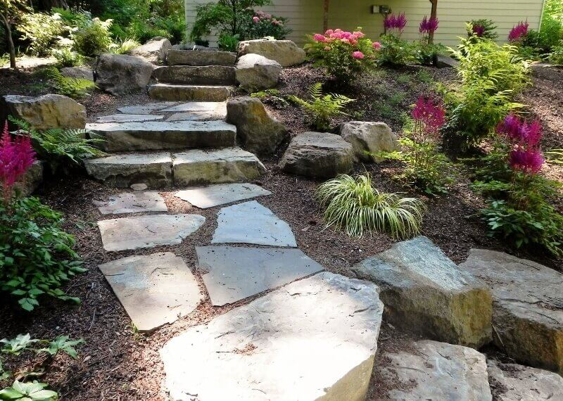 These stone steps use rough cut stones buried in dirt as stepping stones. There are choices that can be had for a setup like this. If you keep up on pulling weeds and maintenance you can have a clean look, but you may also choose to let the plants grow for a wild and natural appeal.