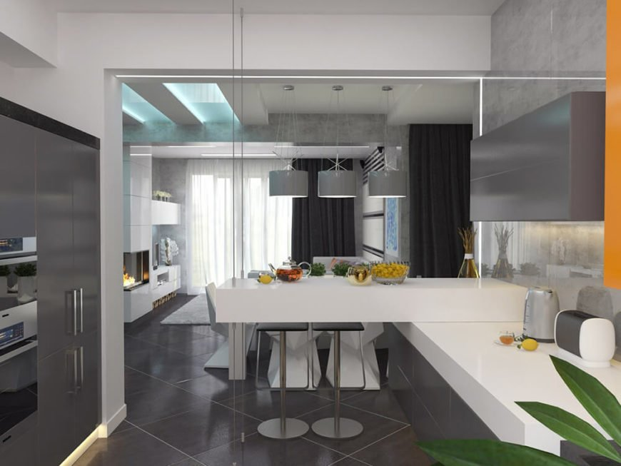 Here we see the dining area from within the kitchen. Bold white glossy countertops meet slate grey in this brightly minimalist space. On both sides, sleek grey cabinetry fills the periphery.
