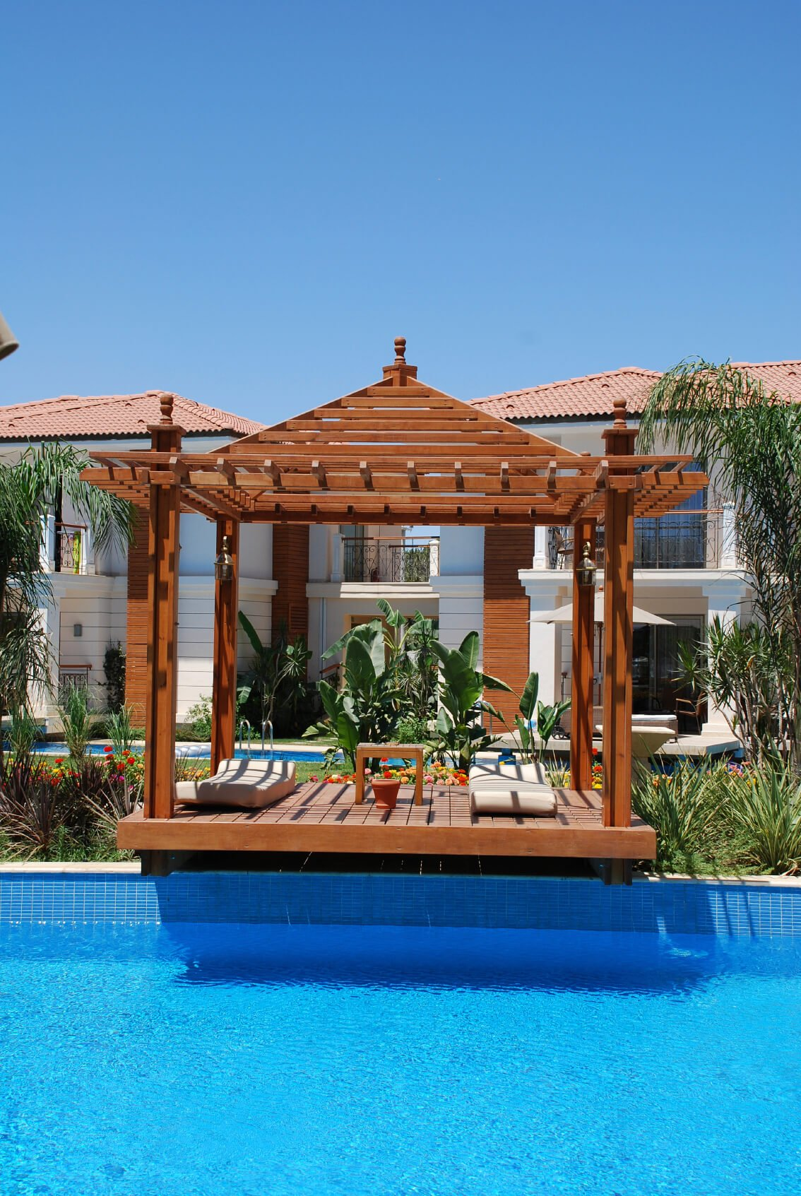This gazebo with relaxed patio furniture has an edge that hangs over the pool. You can dive right into the water from there when you are ready to jump back in.