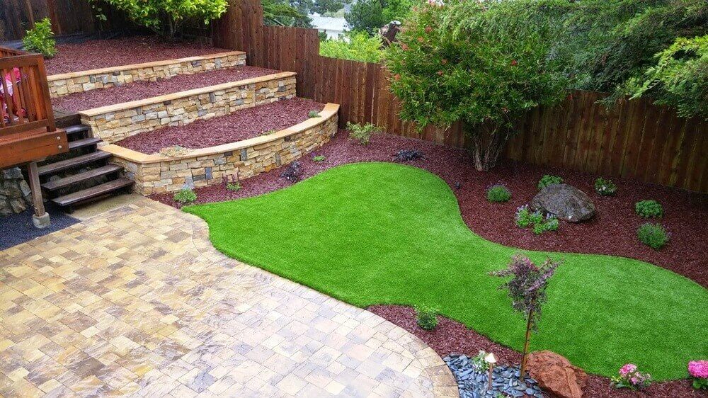 Even a small patch of grass sod can make an impression. This yard has a lovely unique shaped patch of grass.The grass is perfectly maintained and appealing.
