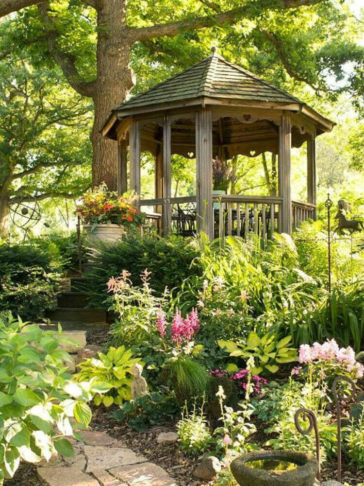 This simple gazebo with natural wood finish is nearly swallowed by the greenery around it. This is a spectacular forest getaway.