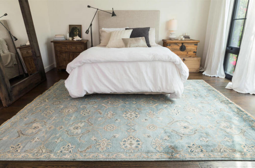 A pretty woven rug with a chic border design adds refined style to a bedroom or living space.