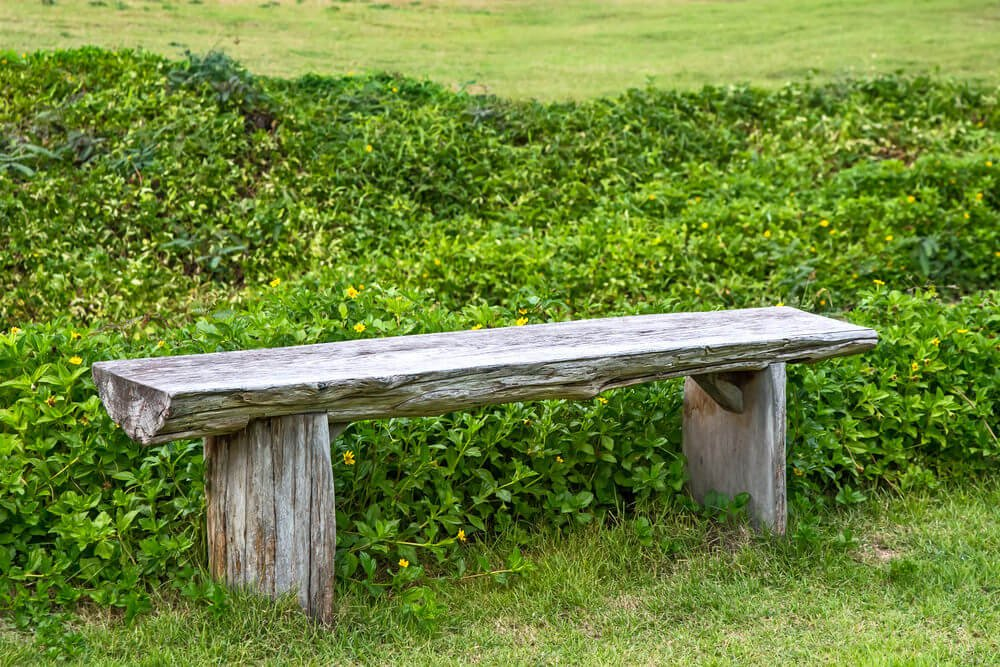 A simple long wooden bench with no arms or back rest. This is made from one slab of wood cut in half lengthwise.