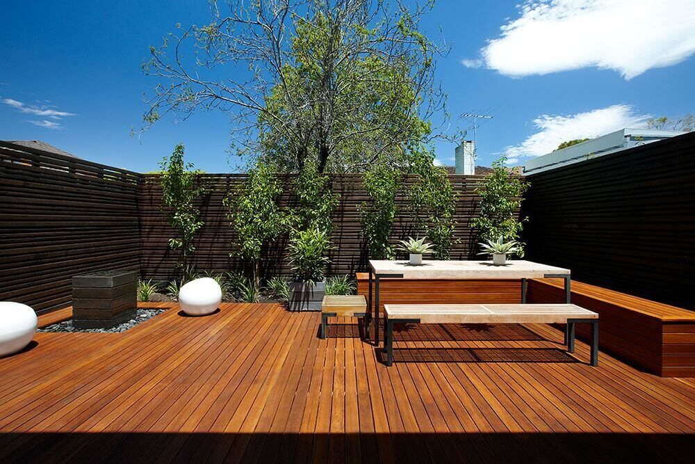This small outdoor area is comprised mostly of deck. On the far end a small tree garden brings life to the space. Even in this modern and sleek design the natural bloom of the trees fits in well.