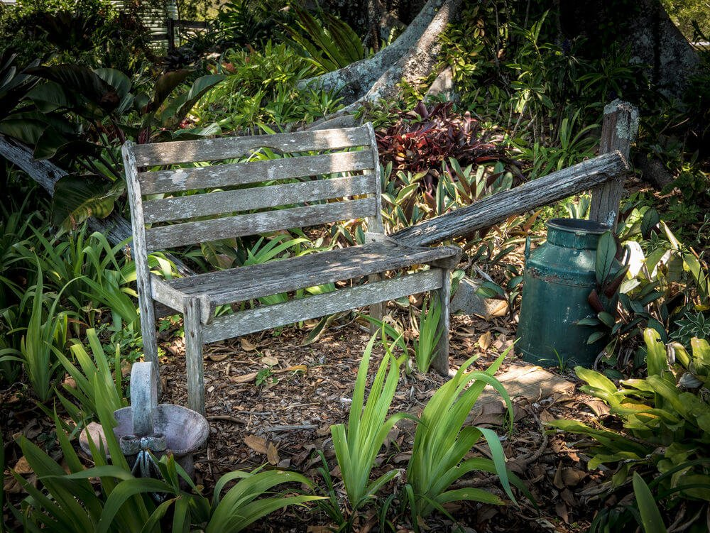 A rustic view of an old and almost worn out bench with a rusted container alongside.