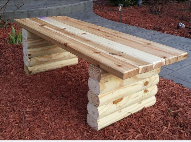 A sleek and creative sleeper bench in a garden spread with mulch. This one is made of a mix of boards and small logs.