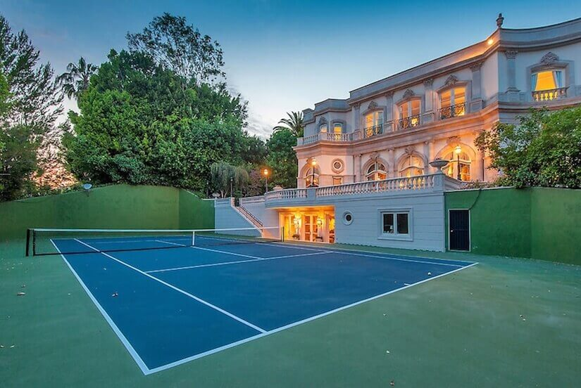 Here is a lovely tennis court that almost looks like a professional arena. There is a well lit, cozy viewing area and the whole court is sunken into the ground to help contain the ball after a wild serve.