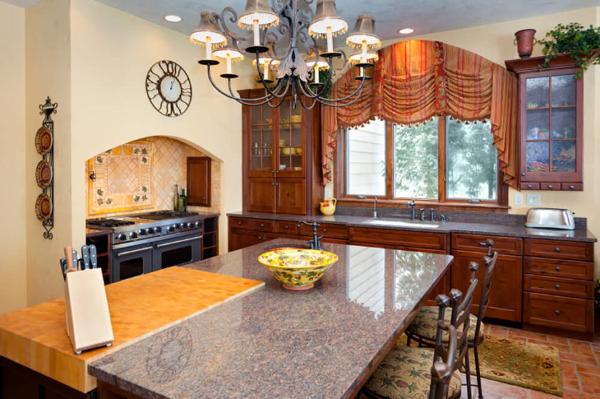 This kitchen has a wide range of colors in its palette, from warm beiges and browns to lighter tans, extending to the greys and whites in the stove top island.