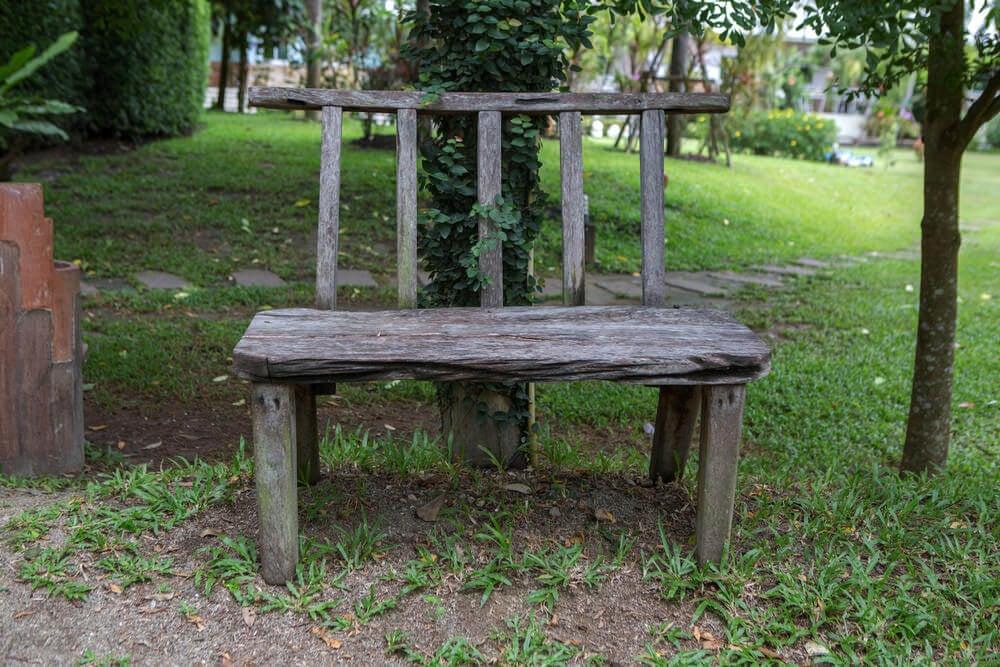 An armless wooden garden bench resting under a tree.