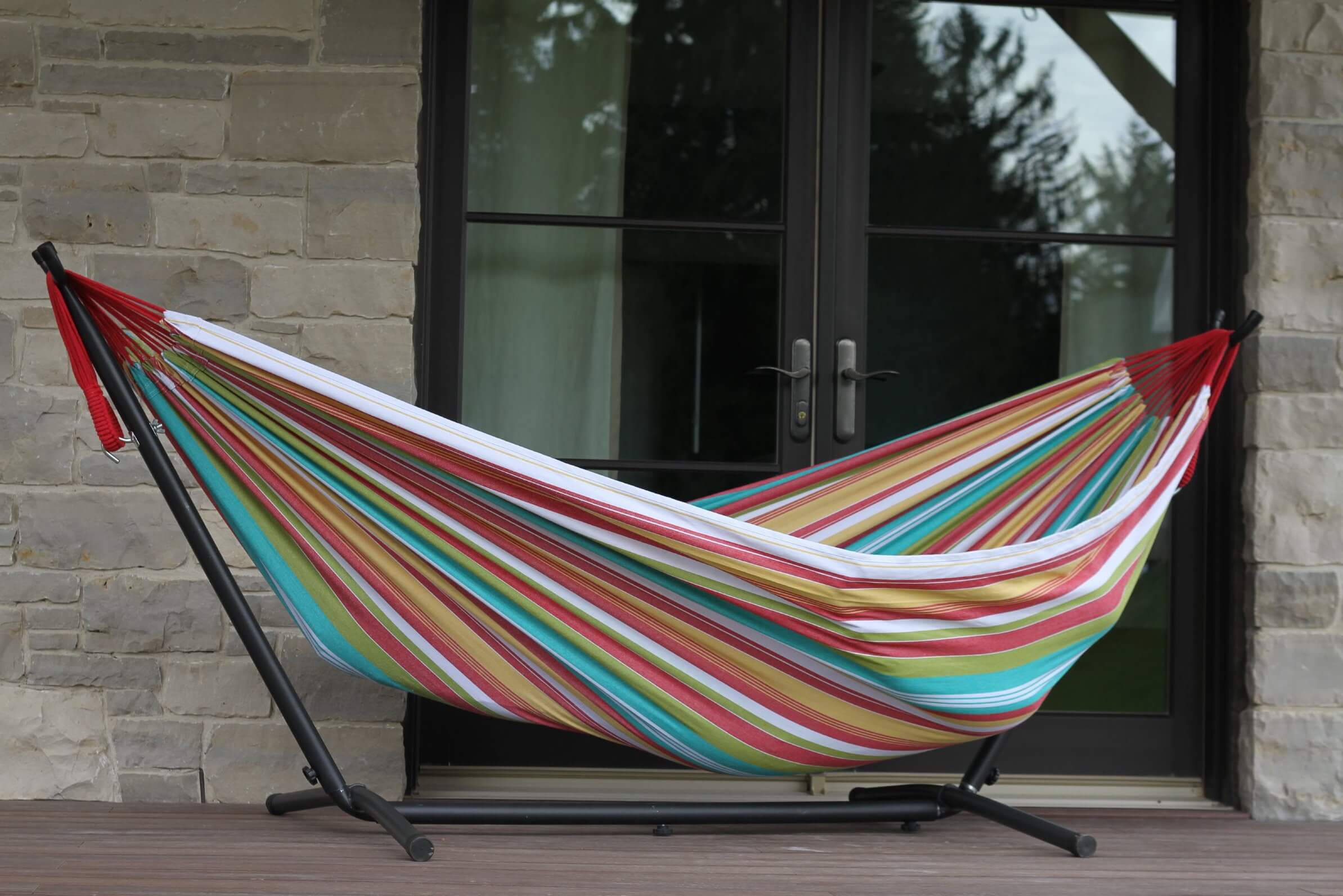 This cloth hammock is a simple design that allows occupants to sink deep down. The absence of wooden splitters on the ends, and the single attaching point on each side, lets this hammock fold and make a cozy cocoon.