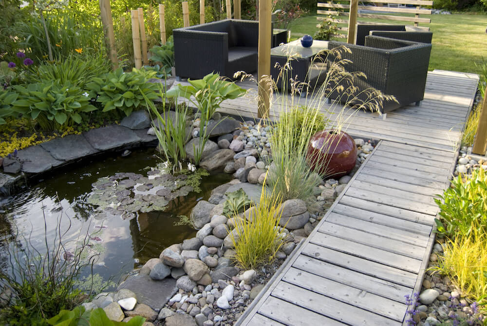 This space has a couple of different kinds of grass. The sod on the far end creates a nice open space for kids to play. In the pond area there are some tall grasses to make the water feature feel more wild and natural.