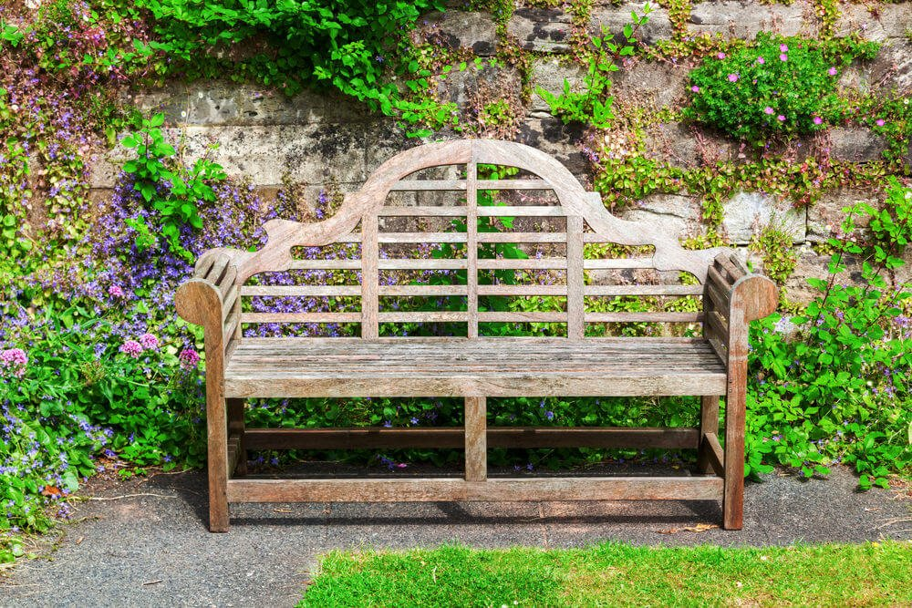 A curvy wooden garden bench still standing proud despite its faded and worn out appearance. This can still accommodate any nature lovers who want to enjoy the flowers.
