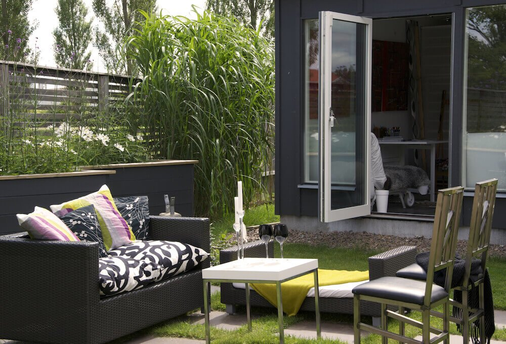 This small area has a patio that is a mix of stone slabs and grass sod. Grass can be cool and soft to the touch while the stone can soak up the sun and be warm on feet, making a great complimentary pair.