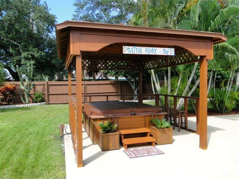 This gazebo has fences to create an isolated and solitary hot tub space. This makes for a great spot where you can escape to shut yourself off from the world, even if only by a bit of fencing.
