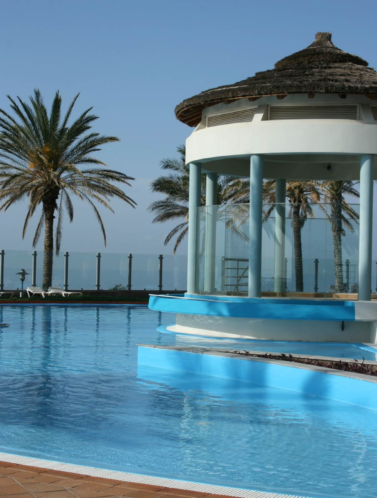This poolside gazebo has a great view of the pool and the surrounding area all while being protected by a wonderful glass wall. This will keep people who don't want to be in the pool dry.
