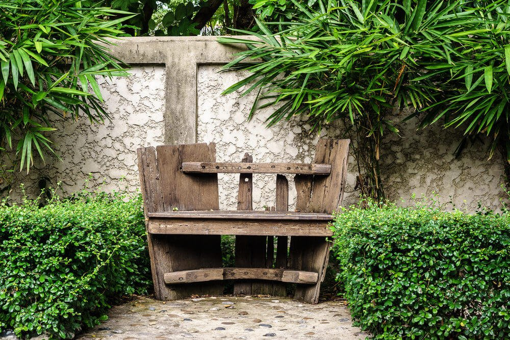 A worn out and shabby chic style garden bench in a green garden area.