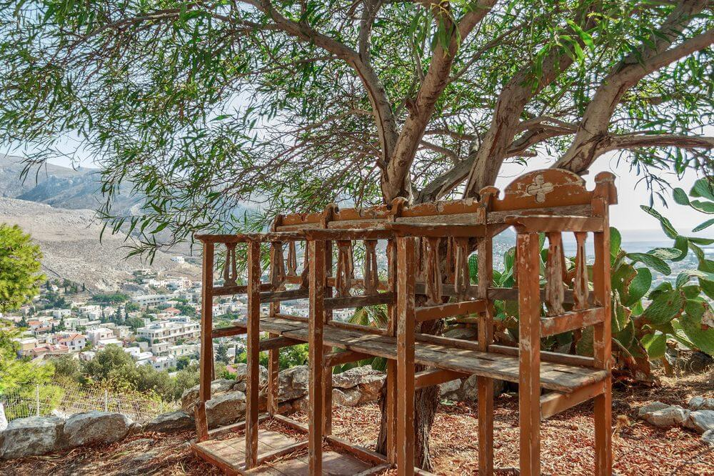 A set of high rise chairs showing the wear and tear of years. An overlooking view of the village below is even made more enjoyable in these.