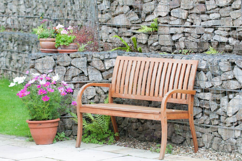 Behind this wooden garden bench is a crushed rock retaining wall enclosed in wire mesh.