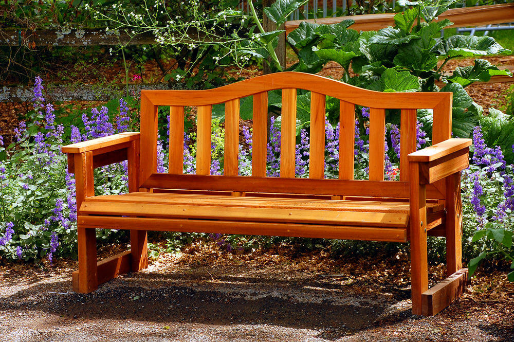 A newly treated and varnished wooden garden bench standing freely in front of purple hyacinths.