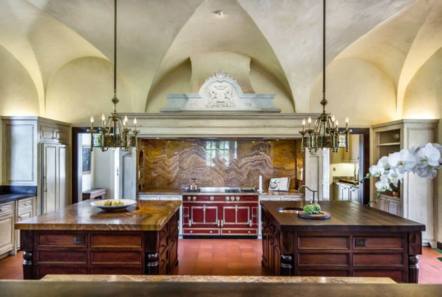 This kitchen has multiple islands adorned with detailed and curved ornamentation. Even the ceiling has a number of curves and natural lines.