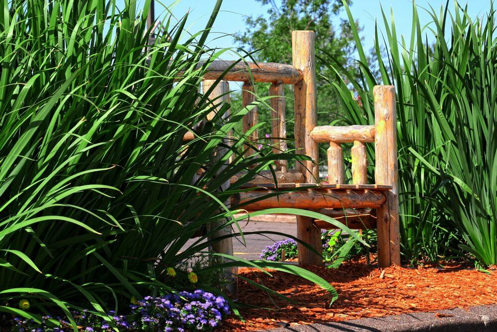 Smaller logs were used to build this mini log garden bench hiding in between high foliage.
